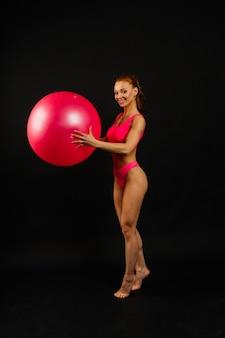 Mulher jovem em forma se exercitando com uma bola de fitness sobre um fundo escuro