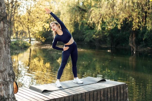 Mulher jovem em forma se exercitando na esteira do parque