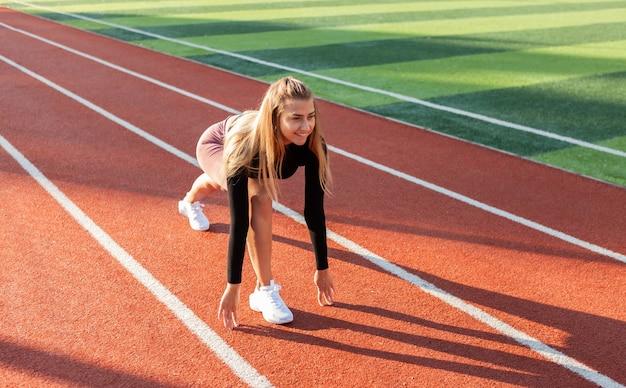 Mulher jovem em forma se preparando para uma corrida baixa no estádio