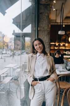 Mulher jovem em frente a janelas em um café