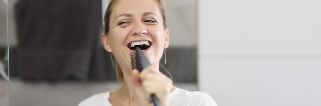 Mulher jovem em frente ao espelho cantando para a escova de cabelo no banheiro