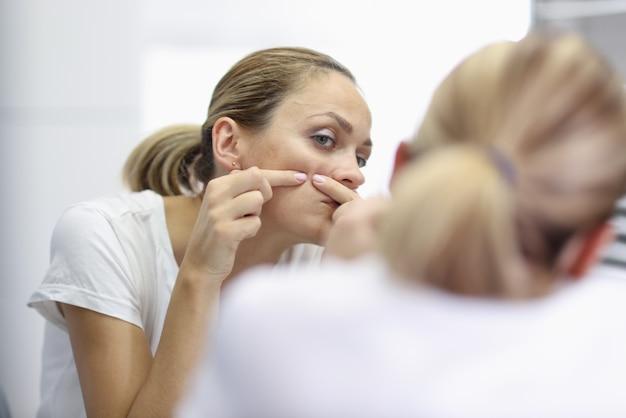 Mulher jovem em frente ao espelho e espremendo espinhas