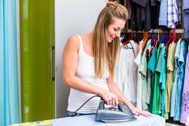 Mulher jovem em frente ao guarda-roupa passando a roupa com ferro