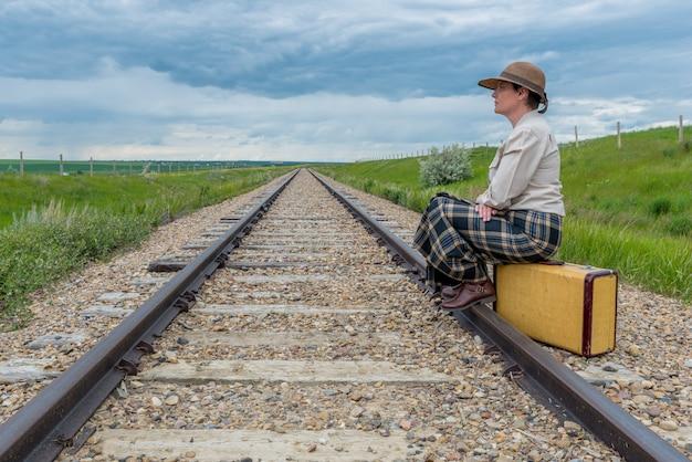 Mulher jovem, em, histórico, vestido, sentando, ligado, mala vintage, ligado, trilha via férrea, olhar, ahead-journey, conceito