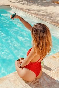 Mulher jovem em maiô inteirinho tirando selfie na beira de uma piscina