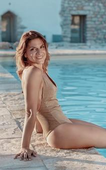 Mulher jovem em maiô relaxando ao lado da piscina close-up