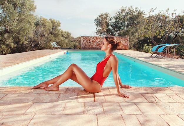 Mulher jovem em maiô vermelho ao lado de uma piscina