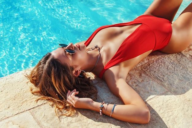 Mulher jovem em maiô vermelho relaxando ao lado de uma piscina de perto