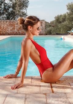 Mulher jovem em maiô vermelho relaxando perto de uma piscina Foto Premium