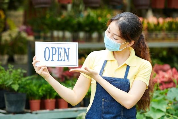 Mulher jovem em máscara médica abrindo o viveiro de plantas e mostrando sinal para convidar clientes