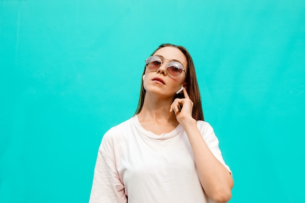 Mulher jovem, em, óculos de sol, com, fones ouvido