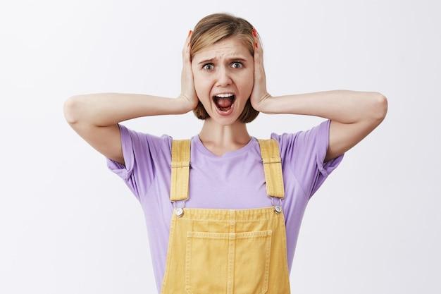 Mulher jovem em pânico gritando em negação, olhando com uma cara de horror em pânico