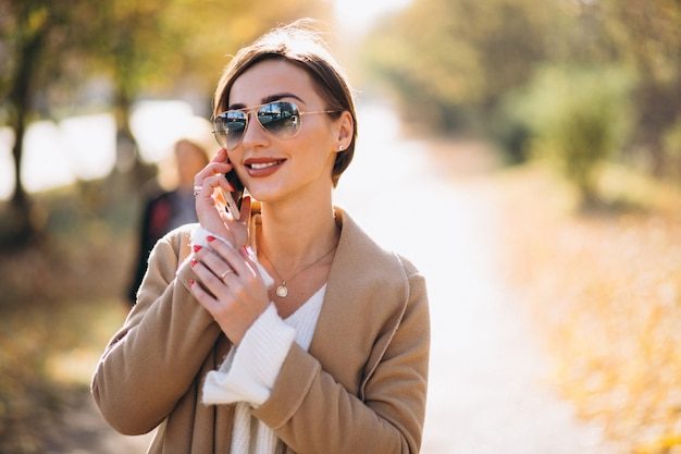 Mulher jovem, em, parque outono, usando, telefone