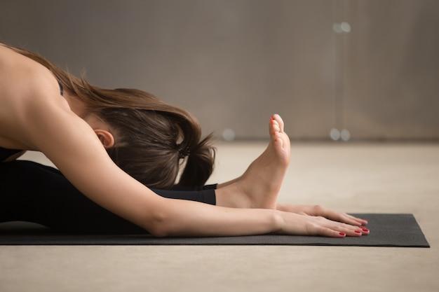 Mulher jovem, em, paschimottanasana, pose, cinzento, estúdio, fundo, c