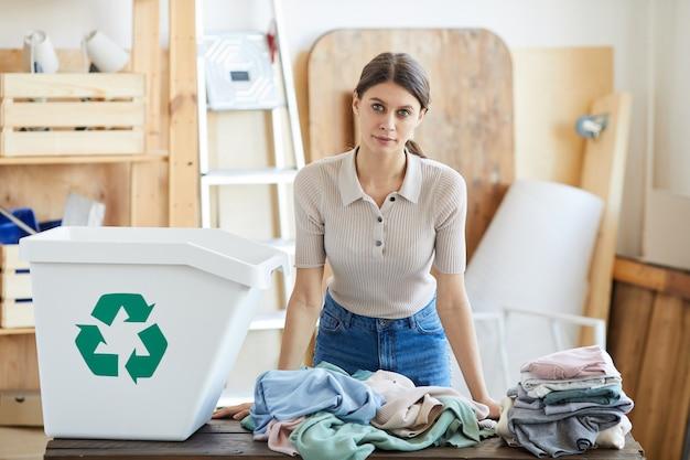 Mulher jovem em pé à mesa olhando para a câmera enquanto separa suas roupas velhas em recipientes