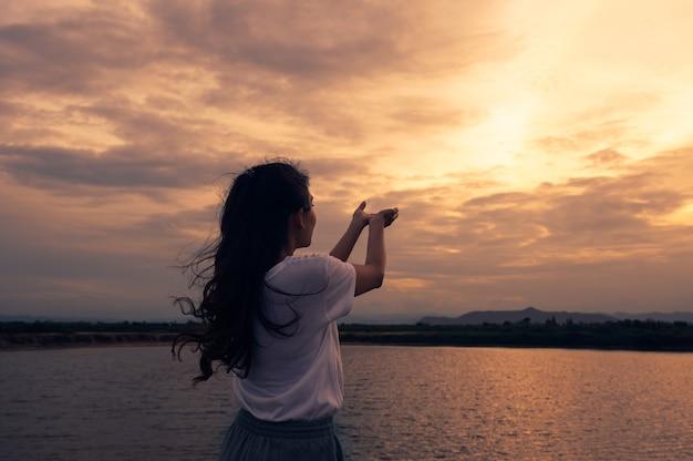 Mulher jovem em pé com as mãos estendidas, orando pela bênção com o céu do sol. conceito de religião