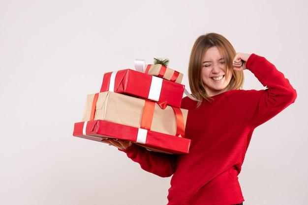 Mulher jovem em pé com os presentes nas mãos
