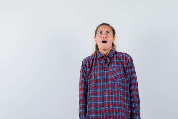 Mulher jovem em pé e gritando em uma camisa xadrez e parecendo assustada