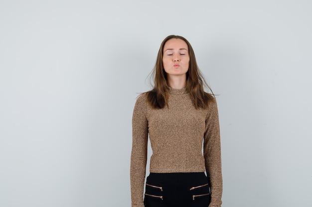 Mulher jovem em pé e mandando beijos em um suéter dourado dourado e calça preta e parecendo charmosa