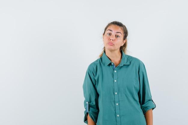 Mulher jovem em pé e posando na frente com uma blusa verde e parecendo uma fofa