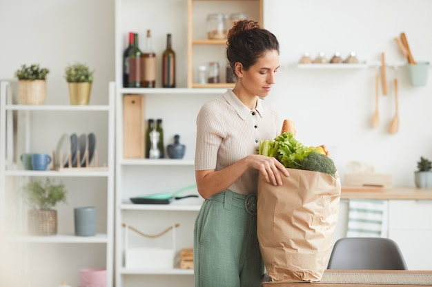 Mulher jovem em pé na cozinha comprando comida em um saco de papel