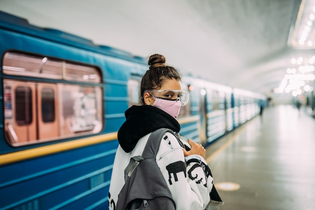 Mulher jovem em pé na estação com máscara protetora médica