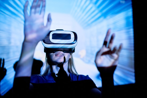 Mulher jovem em pé na luz azul e jogando um jogo virtual com óculos de realidade virtual, imagens 3d virtuais sendo exibidas na tela de projeção