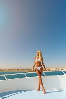 Mulher jovem em pé no convés de um barco em mar aberto em um dia ensolarado de verão