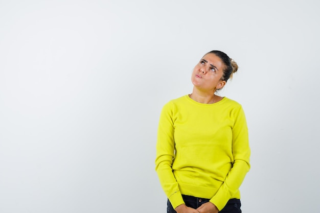 Mulher jovem em pé, olhando para cima e posando para a câmera com um suéter amarelo e calça preta e parecendo pensativa