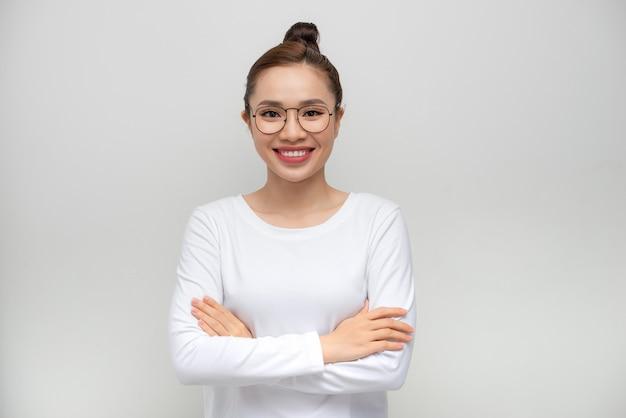 Mulher jovem em pé sobre uma parede branca isolada com rosto feliz e sorrindo com os braços cruzados