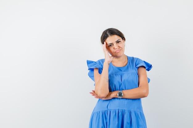 Mulher jovem em pose pensativa, com um vestido azul e um olhar sombrio