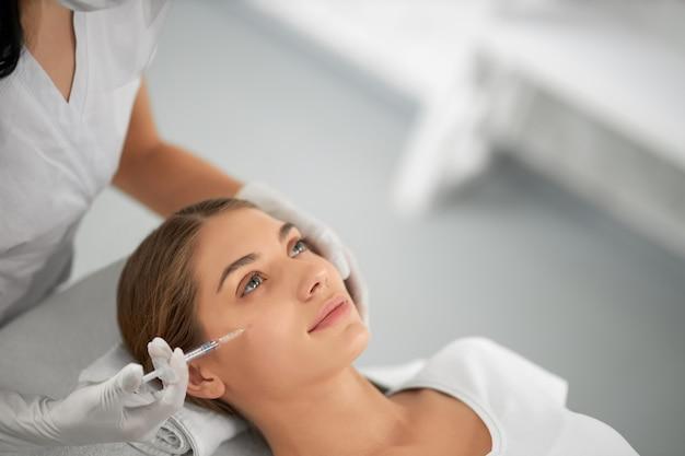 Mulher jovem em procedimento anti-envelhecimento em salão de beleza