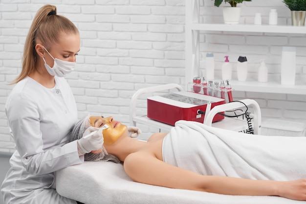 Mulher jovem em procedimento de limpeza de rosto em salão