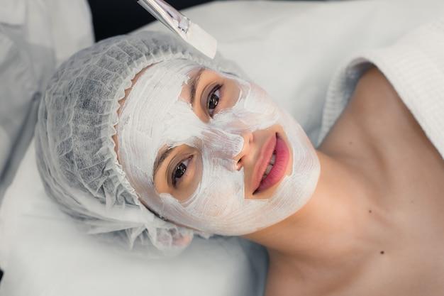 Mulher jovem em procedimentos de spa aplicando máscara