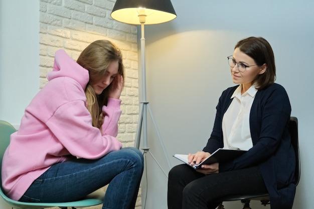 Mulher jovem em reunião com psicóloga, aluna contando a ela problemas, terapeuta, saúde mental da juventude