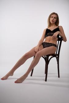 Mulher jovem em roupa íntima de renda sexy, sentada em uma cadeira, foto em uma superfície branca