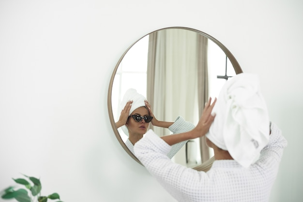 Mulher jovem em roupão de banho com uma toalha branca na cabeça e óculos de sol pretos olhando no espelho do banheiro