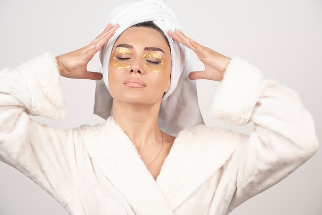 Mulher jovem em roupão de banho e tapa-olhos cosméticos posando.