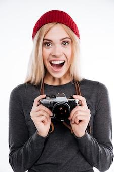 Mulher jovem em roupas casuais em pé e segurando a câmera retro