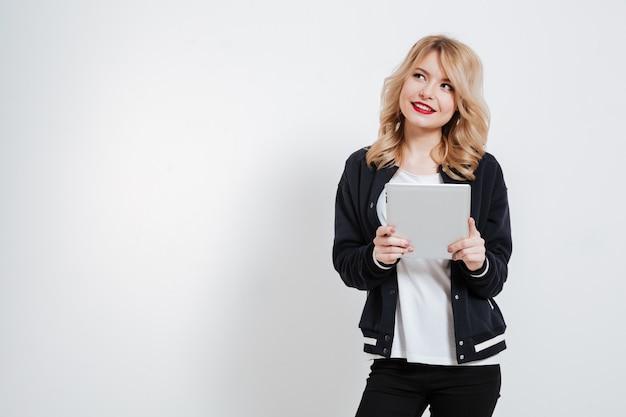 Mulher jovem em roupas casuais, pensando e segurando o computador da tabuleta