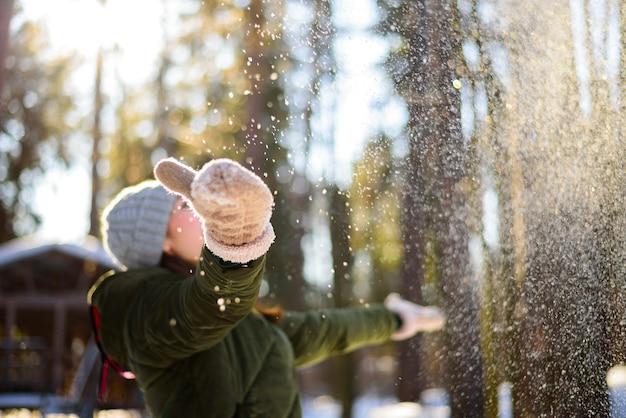 Mulher jovem em roupas de inverno brincando com neve na floresta.