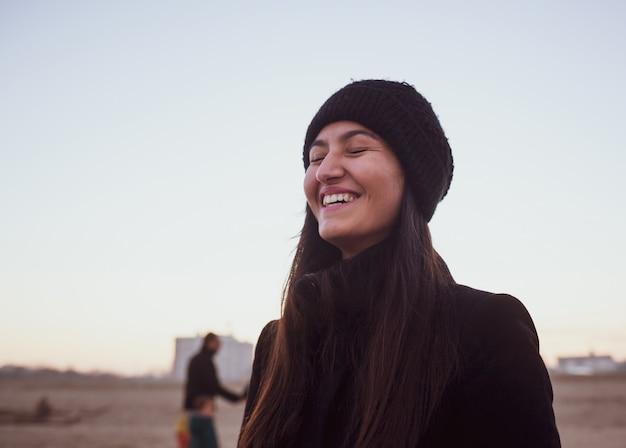 Mulher jovem em roupas de inverno com chapéu de lã, sorrindo com os olhos fechados.