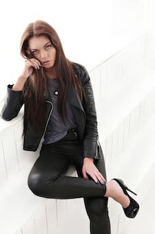 Mulher jovem em roupas de outono de couro preto