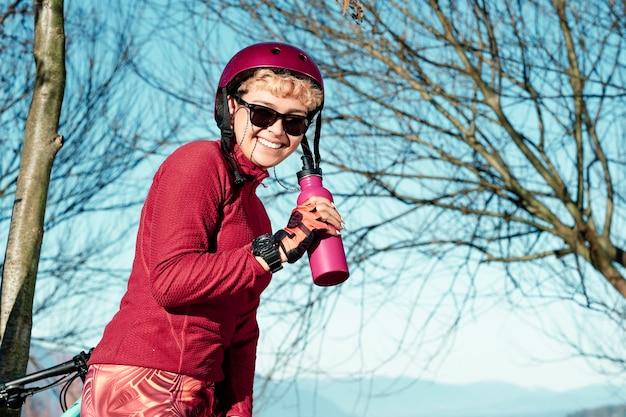 Mulher jovem em roupas esportivas e capacete de bicicleta descansando para beber água