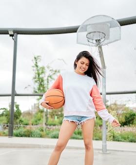 Mulher jovem em roupas esportivas jogando basquete com uma cesta no fundo