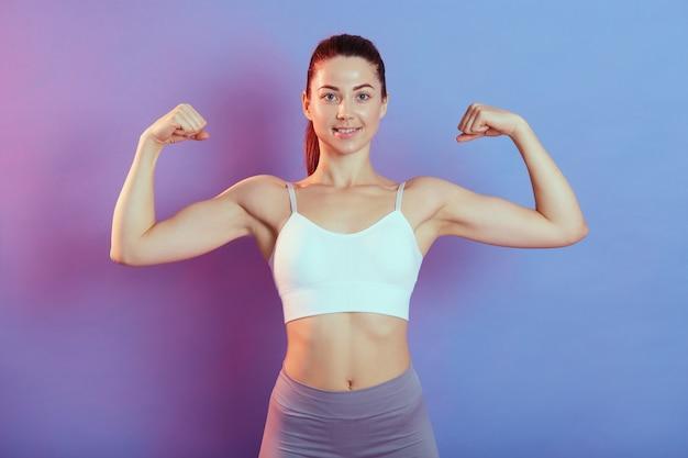 Mulher jovem em roupas esportivas levanta os braços e mostra seus músculos. senhora de esportes, estando envolvida em fitness, em pé contra um fundo de néon, olhando para a câmera com um sorriso feliz.