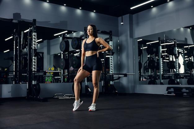 Mulher jovem em roupas esportivas na academia com espelhos