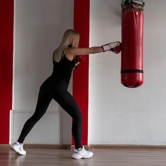 Mulher jovem em roupas esportivas pretas com tênis elegantes e luvas de boxe vermelhas vencendo um saco de pancadas em uma academia moderna