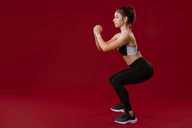 Mulher jovem em roupas esportivas pretas, fazendo exercícios em uma parede vermelha.