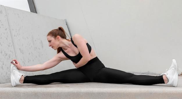 Mulher jovem em roupas esportivas se exercitando ao ar livre